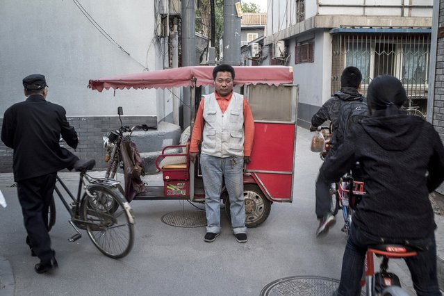 This photo taken on April 22, 2017 shows a rickshaw driver (C) posing in Beijing. (Photo by Fred Dufour/AFP Photo)