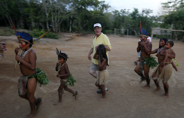 A tourist dances with members of the Amazonian Tatuyo tribe in their village in the Rio Negro (Black River) near Manaus city, a World Cup host city, June 23, 2014. Because of their proximity to host city Manaus and their warm welcome, the Tatuyo have enjoyed three weeks of brisk business thanks to the World Cup. Usually, they host between 10 and 30 tourists a day. During the World Cup, this number has rocketed to 250 a day, They have become richer and other communities now come to them to sell them juices and fishes. (Photo by Andres Stapff/Reuters)