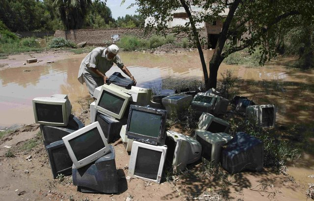 A worker moves old computer monitors after heavy rainfall caused flooding in Peshawar, Pakistan, July 27, 2015. Flash flooding caused by torrential monsoon rains has killed at least 28 in Pakistan and affected hundreds of thousands of people, according to aid agencies, with further downpours expected in the coming days. (Photo by Khuram Parvez/Reuters)