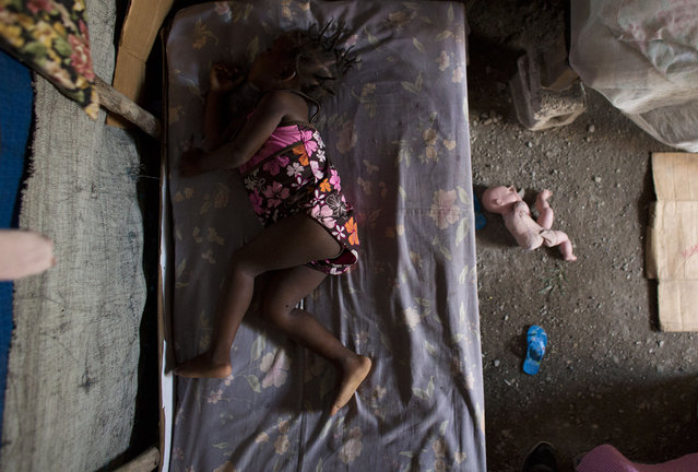 In this June 26, 2015 photo, two-year-old Naika Pierre sleeps on a bed in the dirt-floor tent where she lives with her parents in one of the remaining post-earthquake camps in Cite Soleil, Port-au-Prince, Haiti. When the earthquake struck in 2010, the building where Naika's parents were living in Cite Soleil was heavily damaged and they were forced to move into a tent camp inside the slum. Five years later, they are still living under pieced-together tarps, with cardboard and cinderblocks, the only buffer from a dirt floor that can turn to mud in the rains. (Photo by Rebecca Blackwell/AP Photo)