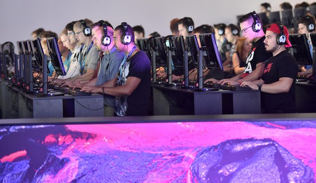 Participants  play the latest video games at the gamescom  computer game fair  in Cologne, Germany, Wednesday, August 5, 2015. (Photo by Martin Meissner/AP Photo)