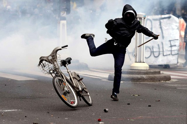 A demonstrator kicks a Velib bicycle during a protest against proposed labour reforms in Paris on June 14, 2016. Strikes closed the Eiffel Tower and disrupted transport in France on June 14 as tens of thousands prepared to march against labour reforms with the Euro 2016 football championship in full swing. (Photo by Alain Jocard/AFP Photo)