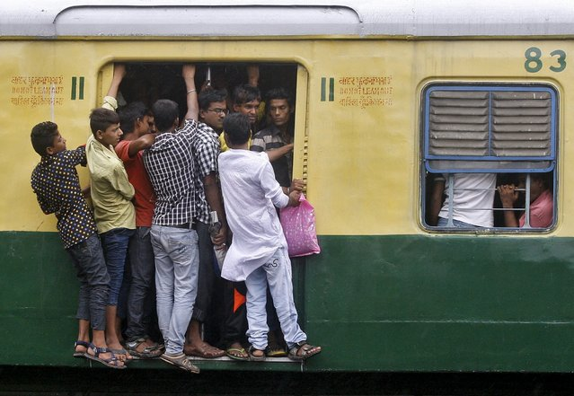 Commuters stand at an open doorway of a suburban train during the morning rush hour in Kolkata, India, July 31, 2015. India is set to overtake China and become the world's most populous country in less than a decade - six years sooner than previously forecast, the United Nations said on Wednesday. (Photo by Rupak De Chowdhuri/Reuters)