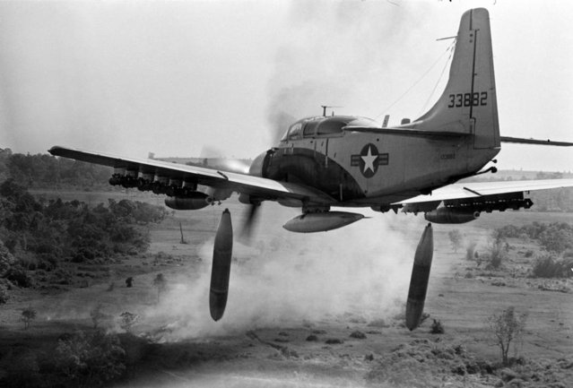 Flying low over the jungle, an A-1 Skyraider drops 500-pound bombs on a Viet Cong position below as smoke rises from a previous pass at the target, Dec. 26, 1964
