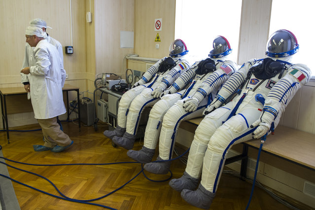 Space suits of NASA astronaut Randy Bresnik, ESA astronaut Paolo Nespoli and Russian cosmonaut commander Sergei Ryazansky are being tested at an assembling department of the Russian leased Kazakh Baikonur cosmodrome on July 17, 2017. Soyuz MS-05 launch is scheduled on July 28, 2017. (Photo by AFP Photo/Stringer)