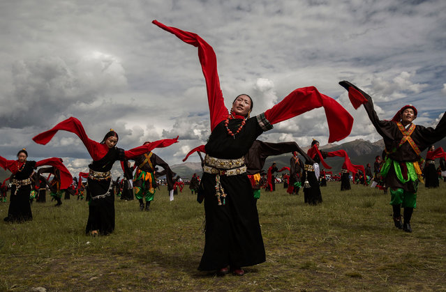 Ethnic Tibetans wearing traditional costume dance on July 25, 2015 at a local government sponsored festival on the Tibetan Plateau in Yushu County, Qinghai, China. (Photo by Kevin Frayer/Getty Images)