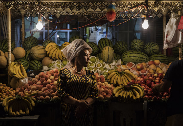 An ethnic Uyghur woman waits for customers at her fruit stand  on June 27, 2017 in the old town of Kashgar, in the far western Xinjiang province, China. Kashgar has long been considered the cultural heart of Xinjiang for the province's nearly 10 million Muslim Uyghurs. At an historic crossroads linking China  to Asia, the Middle East, and Europe, the city has  changed under Chinese rule with government development, unofficial Han Chinese settlement to the western province, and restrictions imposed by the Communist Party. Beijing says it regards Kashgar's development as an improvement to the local economy, but many Uyghurs consider it a threat that is eroding their language, traditions, and cultural identity.  The friction has fuelled a separatist movement that has sometimes turned violent, triggering a crackdown on what China's government considers 'terrorist acts' by religious extremists.  Tension has increased with stepped up security in the city and the enforcement of measures including restrictions at mosques. (Photo by Kevin Frayer/Getty Images)