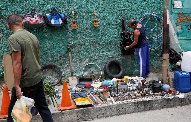 A man sells second-hand goods along a street in Caracas, Venezuela, June 25, 2016. (Photo by Marco Bello/Reuters)