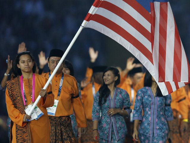 Malaysia's flag bearer Muhammad Imaadi Aba Aziz during the opening ceremony for the Commonwealth Games 2014 in Glasgow, Scotland, Wednesday July 23, 2014. The Malaysian team were wearing black armbands to mark the recent crash of Malaysian Airlines plane MH17. (Photo by Frank Augstein/AP Photo)