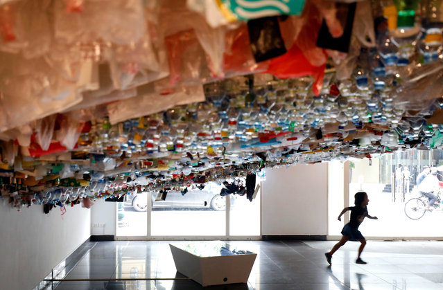 A girl runs during the exhibition of a hanging art installation made from scraps of plastic bags, bottles, cans and containers at an exhibition entitled Reduce, at the French Cultural Center in Hanoi, Vietnam on August 2, 2019. (Photo by Reuters/Kham)