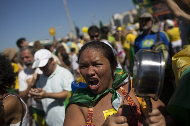 A woman shouts slogans as bangs on a pan during an anti-government protest demanding the impeachment of Brazil's President Dilma Rousseff in Rio de Janeiro, Brazil, Sunday, August 16, 2015. (Photo by Leo Correa/AP Photo)