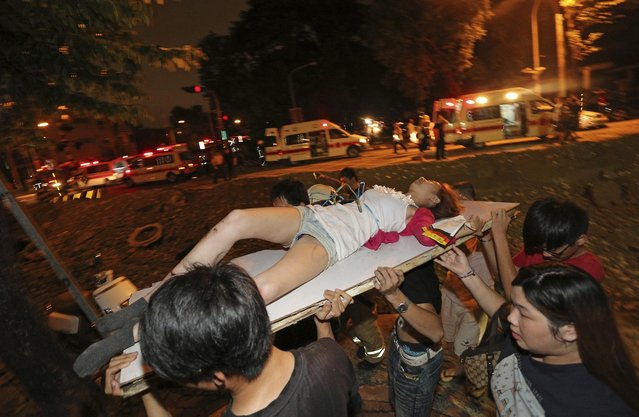 A victim in a gas explosion from an underground gas leak is carried from the rubble in a main street in Kaohsiung, Taiwan, early Friday, August 1, 2014.  A massive gas leakage early Friday caused five explosions that killed several people and injured over 200 in the southern Taiwan port city of Kaohsiung. (Photo by AP Photo)