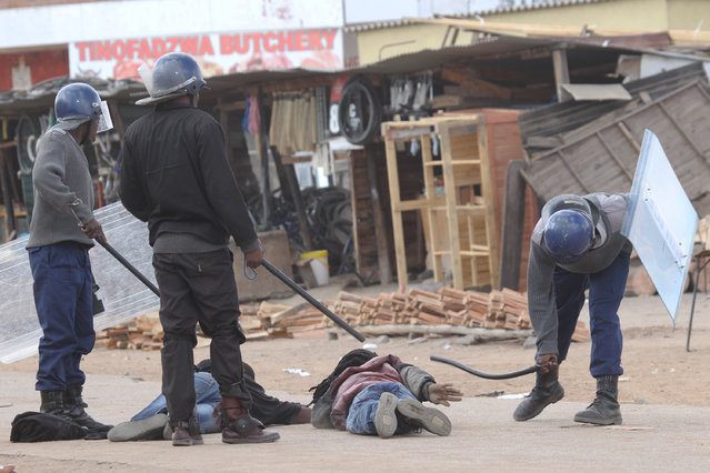 Armed Zimbabwean police beat alleged rioters in Harare, Monday, July, 4, 2016. (Photo by Tsvangirayi Mukwazhi/AP Photo)