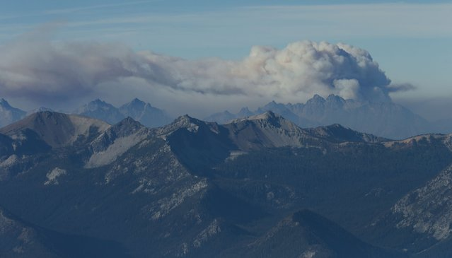 In this aerial photo, smoke from a wildfire rises above the North Cascades in Washington, Thursday, August 20, 2015. Firefighters on several fronts are fighting against raging wildfires advancing on towns in the north-central part of the state. (Photo by Bettina Hansen/The Seattle Times via AP Photo)