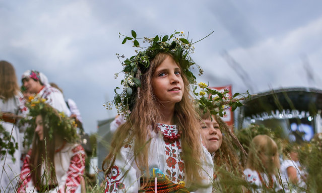 A picture made available on 07 July 2016 shows a Ukrainian young girl wearing a flower diadem during the traditional Slavic celebrations of Ivana Kupala in Kiev, Ukraine, 06 July 2016. Ivana Kupala is celebrated, during the Summer Solstice, on the shortest night of the year, marking the beginning of summer and is celebrated in Ukraine, Belarus, Poland and Russia on the night of 06 July. People sing and dance around bonfires, playing games and performing traditional rituals. (Photo by Roman Pilipey/EPA)