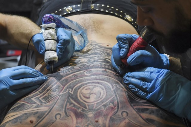 Tattoo artists apply ink on a man' s back during the 6th Siberian Tattoo Festival at Podzemka Loft Park in Novosibirsk, Russia on August 20, 2017. (Photo by Kirill Kukhmar/TASS)