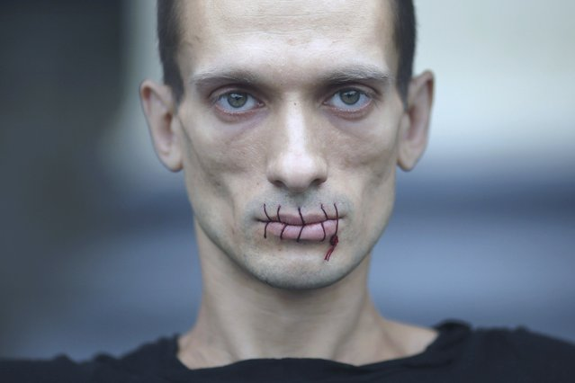 "Artist Pyotr Pavlensky, a supporter of jailed members of russian female punk band ""p*ssy Riot"", looks on with his mouth sewed up as he protests outside the Kazan Cathedral in St. Petersburg, Russia, July 23, 2012. A court on Monday rejected a request to call President Vladimir Putin and the head of the Russian Orthodox Church to testify in the trial of three female punk rockers who derided Putin in a protest in the country's main cathedral, their lawyer said. Picture taken July 23, 2012. (Photo by Trend Photo Agency/Handout/Reuters)"