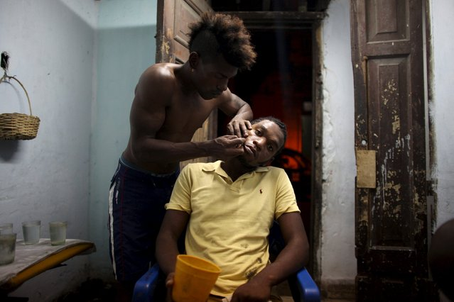 Ifrain Garcia, 23, has his hair cut at home by his friend Joel Drecker, 32, a gardener, in downtown Havana, April 9, 2015. (Photo by Alexandre Meneghini/Reuters)