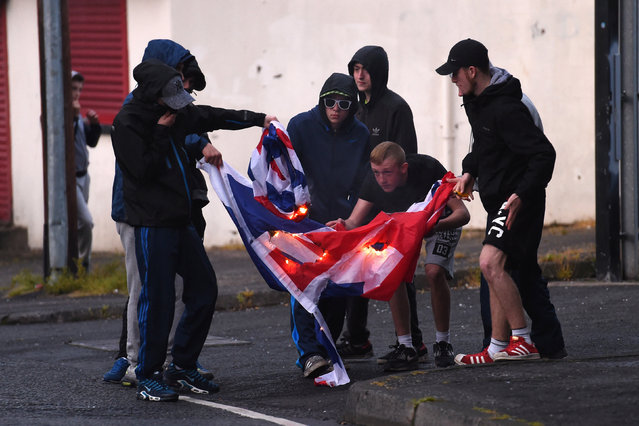 Nationalists in the Ardoyne area are seen setting fire to a British flag after the annual Twelfth of July Orange Order Parade in Belfast, Northern Ireland, July 12, 2016. (Photo by Clodagh Kilcoyne/Reuters)