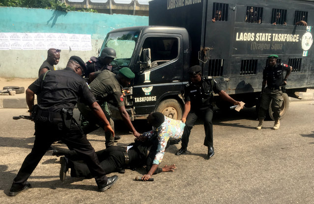 Police officers pull a journalist during an anti-government protest in Lagos, Nigeria on August 5, 2019. (Photo by Nneka Chile/Reuters)