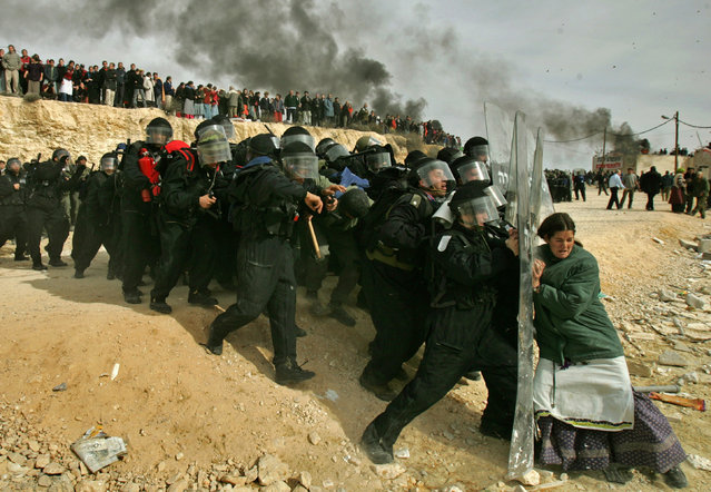 A Jewish settler struggles  with an Israeli security officer during clashes that erupted as authorities evacuated the West Bank settlement outpost of Amona, east of the Palestinian town of Ramallah, in this February 1, 2006, file photo. Oded Balilty of The Associated Press has won the Pulitzer Prize for breaking news photography for his image of a lone Jewish woman defying Israeli security forces as they remove illegal settlers in the West Bank. (Photo by Oded Balilty/AP Photo)