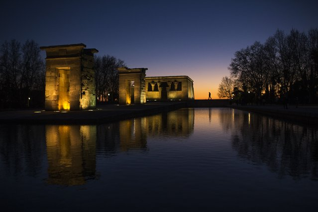 A security guard walks by the Temple of Debod at sunset in Madrid, Spain, Monday, February 29, 2016. The ancient temple, which was originally built in Egypt, was dismantled and relocated in Madrid as a donation from the Egyptian state to Spain in 1968. (Photo by Francisco Seco/AP Photo)