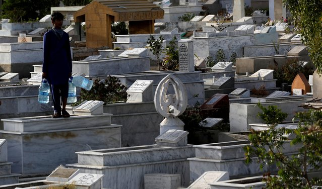 A boy with water-filled containers for sale, stands on a grave while waiting for people, during a lockdown after a government-imposed ban on visiting graveyards for Shab-e-Barat festival, following the spread of coronavirus disease (COVID-19) in Karachi, Pakistan on April 8, 2020. (Photo by Akhtar Soomro/Reuters)
