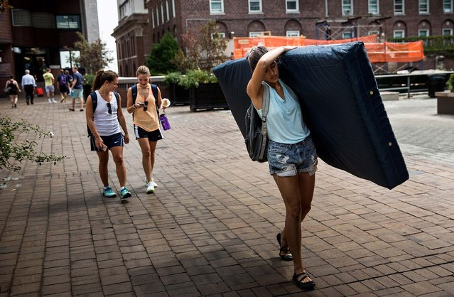 Emma Sulkowicz, a senior visual arts student at Columbia University, carries a mattress in protest of the university's lack of action after she reported being raped during her sophomore year, on September 5, 2014. Sulkowicz has said she is committed to carrying the mattress everywhere she goes until the university expels the rapist or he leaves. The protest is also doubling as her senior thesis project. (Photo by Andrew Burton/Getty Images)