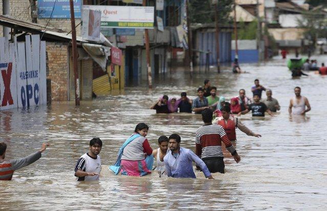 Kashmiri men evacuate women and the elderly from a flooded neighborhood in Srinagar, India, Sunday, September 7, 2014. (Photo by Dar Yasin/AP Photo)