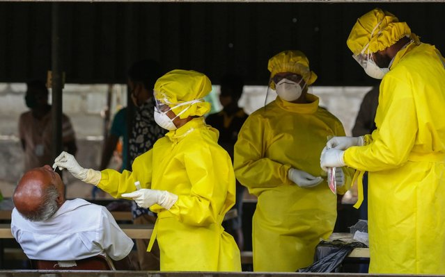 A Sri Lankan health officer wearing protective gear performs a swab test on a municipal worker at the regional municipal office amid the coronavirus pandemic in Colombo, Sri Lanka, 22 April 2020. The Government has implemented a curfew in some parts of the island until further notice in order to slow down the spread of the SARS-CoV-2 coronavirus that causes the COVID-19 disease. (Photo by Chamila Karunarathne/EPA/EFE)