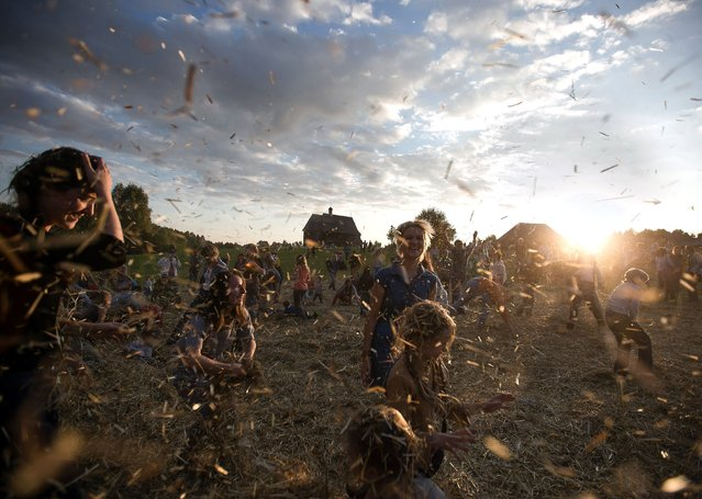 People dance and throw straw during a traditionnal festival in village Ozerco, some 10 km from Minsk, on September 6, 2014. (Photo by Uladz Hrydzin/AFP Photo)