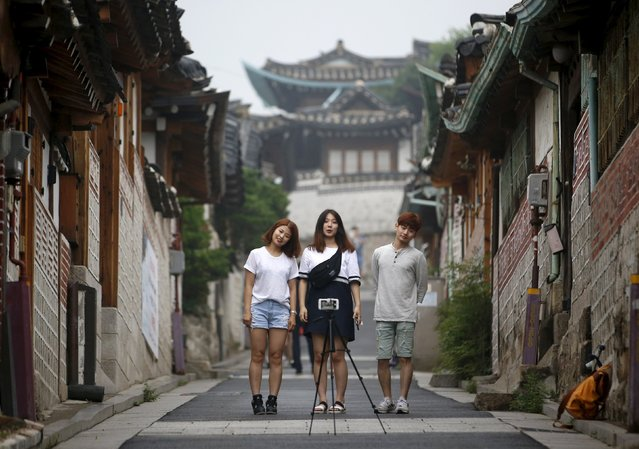 Youths pose for photographs at Bukchon Hanok Village, a traditional village in Seoul, South Korea, July 13, 2015. (Photo by Kim Hong-Ji/Reuters)