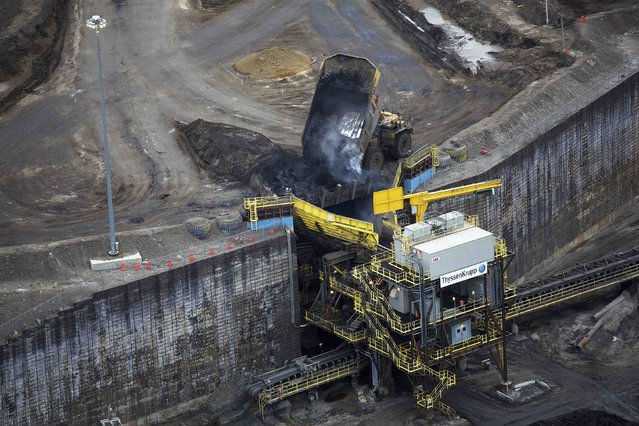 Giant dump trucks dump raw tar sands for processing at the Suncor tar sands mining operations near Fort McMurray, Alberta, September 17, 2014. (Photo by Todd Korol/Reuters)