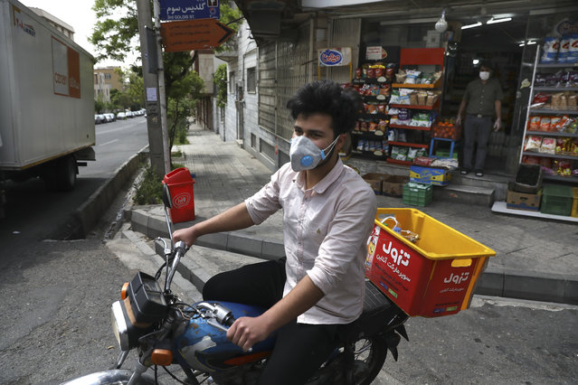 In this Tuesday, April 21, 2020 photo, grocery delivery man Saeed Vatanparast, wearing a protective face mask to help prevent the spread of the coronavirus, leaves on his motorcycle for a delivery, in Tehran, Iran. For some $15 a day, deliverymen don masks and gloves in Iran's capital to zip across its pandemic-subdued streets to drop off groceries and food for those sheltering at home from the virus. (Photo by Vahid Salemi/AP Photo)