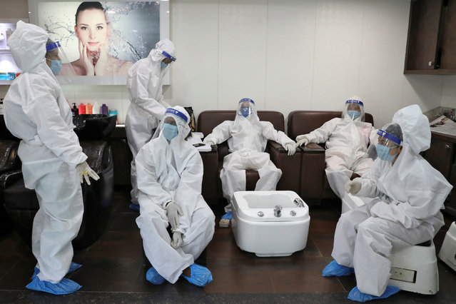 Workers wearing personal protective equipment (PPE) wait for customers inside a salon cum beauty parlour after authorities allowed them to open, during an extended nationwide lockdown to slow the spreading of the coronavirus disease (COVID-19), in Kolkata, India, May 29, 2020. (Photo by Rupak De Chowdhuri/Reuters)