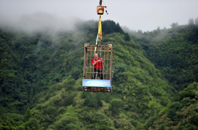 Canadian escape artist Dean Gunnarson performs an escape above a lake in Zhangjiajie, Hunan province, September 19, 2014. Gunnarson, chained, freed himself from a iron cage in 3 minutes 21 seconds during a stunt performance on Friday, according to local media. (Photo by Reuters/China Daily)