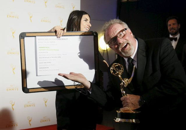 "Producer Thom Beers poses with a sign indicating him as one of the winners of the outstanding unstructured reality award as he holds his award for ""Deadliest Catch"" backstage at the 2015 Creative Arts Emmy Awards in Los Angeles, California September 12, 2015. (Photo by Danny Moloshok/Reuters)"