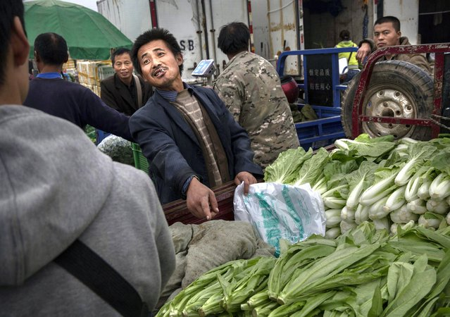 A Chinese vendor makes a deal with a customer at a local market on September 26, 2014 in Beijing, China. (Photo by Kevin Frayer/Getty Images)