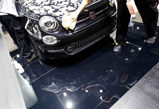 Employees clean a Fiat 500 Abarth during the media day at the Frankfurt Motor Show (IAA) in Frankfurt, Germany, September 14, 2015. (Photo by Kai Pfaffenbach/Reuters)