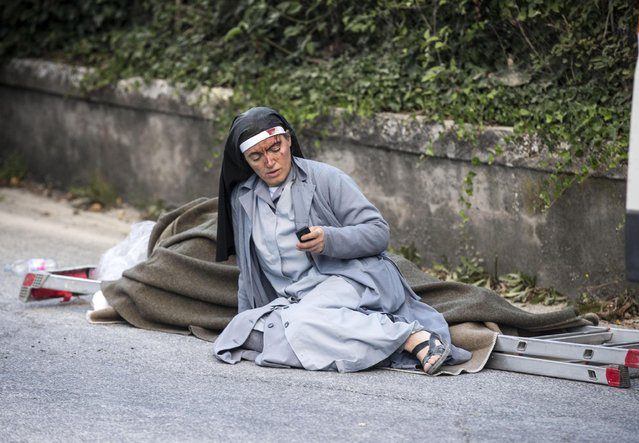 A nun checks her mobile phone as she lies near a victim laid on a ladder following an earthquake in Amatrice Italy, Wednesday, August 24, 2016. The magnitude 6 quake struck at 3:36 a.m. (01:36 GMT) and was felt across a broad swath of central Italy, including Rome where residents of the capital felt a long swaying followed by aftershocks. (Photo by Massimo Percossi/ANSA via AP Photo)