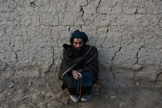 An Internally displaced an Afghan man prays as he sit at a refugee camp in Kabul on November 19, 2017. (Photo by Noorullah Shirzada/AFP Photo)