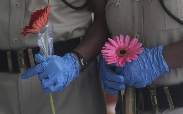 Security officers hold flowers given to them as a gesture of gratitude at the end of a free medical camp in Dharavi, one of Asia's biggest slums, in Mumbai, India, Friday, June 26, 2020. India is the fourth hardest-hit country by the pandemic in the world after the U.S., Russia and Brazil. (Photo by Rafiq Maqbool/AP Photo)