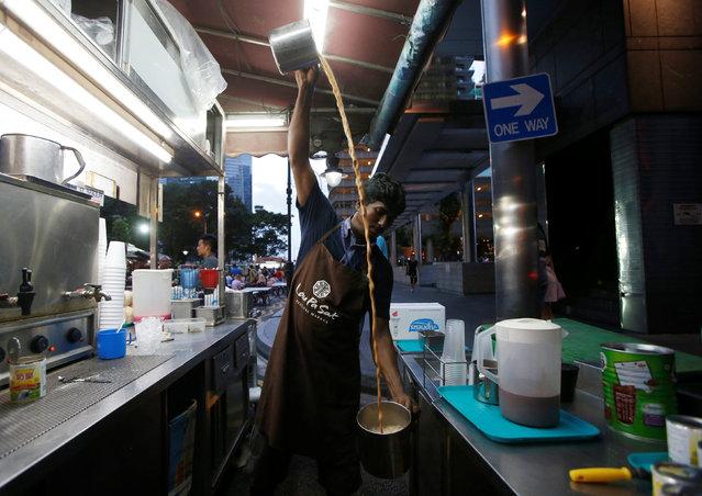 "A hawker ""pulls"" tea at his Teh Tarik stall at Lau Pa Sat food centre in Singapore July 29, 2016. (Photo by Edgar Su/Reuters)"