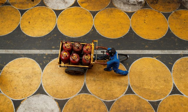 A man pushes a cart filled with liquefied petroleum gas (LPG) cylinders on a street painted with circles for people to maintain social distancing after a few restrictions were relaxed during an extended lockdown to slow the spread of the coronavirus disease (COVID-19) in Mumbai, India, July 1, 2020. (Photo by Francis Mascarenhas/Reuters)