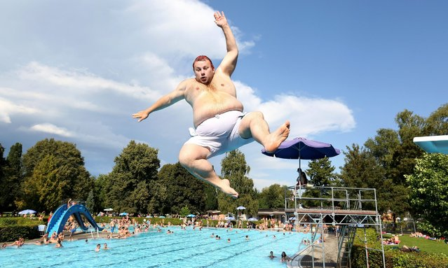 Thomas jumps into the water from a spring board at a public swimming pool in Mengen, Germany, 28 August 2016. (Photo by Thomas Warnack/EPA)