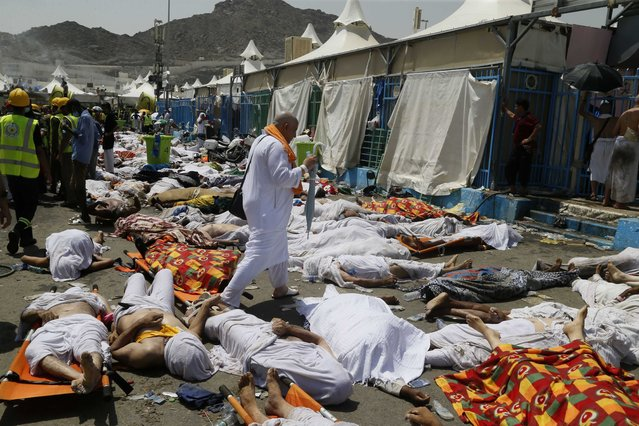 A muslim pilgrim walks through the site where dead bodies are gathered in Mina, Saudi Arabia during the annual hajj pilgrimage on Thursday, September 24, 2015. (Photo by AP Photo)