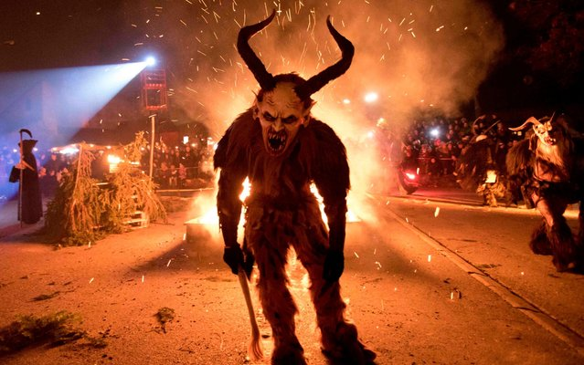 "A participant performs during a procession of ""Krampus"" monsters in Schwadorf, Austria on November 24, 2017 Krampus is traditionally the evil sidekick of Santa, sent to frighten naughty children and ""evil spirits"" in the run- up for Christmas. (Photo by Alex Halada/AFP Photo)"