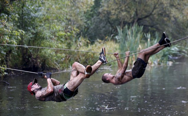 Men cross a channel on ropes as they take part in an extreme run competition in Zhodino, east of Minsk, September 26, 2015. (Photo by Vasily Fedosenko/Reuters)