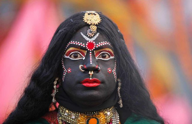 A man, dressed as Hindu Goddess Kali, participates in a religious procession towards the Sangam, the confluence of rivers Ganges, Yamuna and mythical Saraswati, as part of the Mahakumbh festival in Allahabad, India, Sunday, Jan. 6, 2013. Millions of Hindu pilgrims are expected to take part in the large religious congregation on the banks of Sangam during the Mahakumbh festival in January 2013, which falls every 12th year. (AP Photo/Rajesh Kumar Singh)