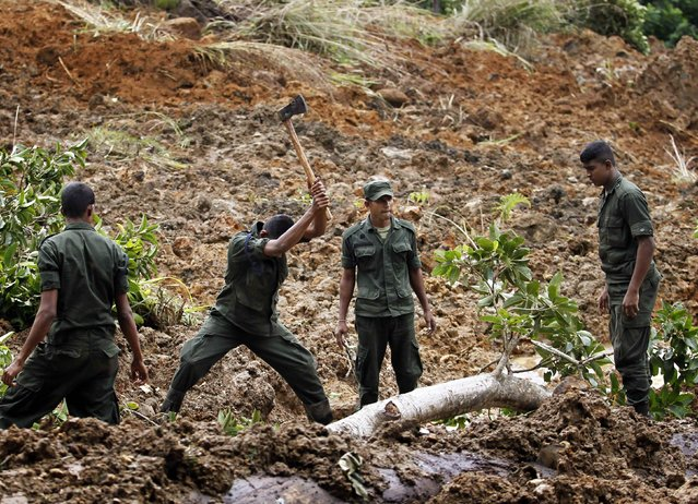 Members of a military rescue team conduct a search at the site of a landslide at the Koslanda tea plantation near Haldummulla October 30, 2014. (Photo by Dinuka Liyanawatte/Reuters)